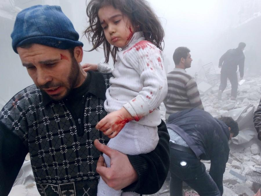 A Syrian man evacuates a child found in the rubble of a building reportedly hit by an explosives-filled barrel dropped by a government forces helicopter on March 18, 2014 in Aleppo. Iran's foreign minister that Tehran is